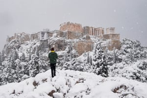 A man takes photos of the Parthenon temple on top the Acropolis hill archaeological site