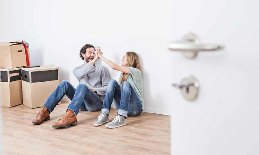 Couple sitting on floor and giving high five, smiling