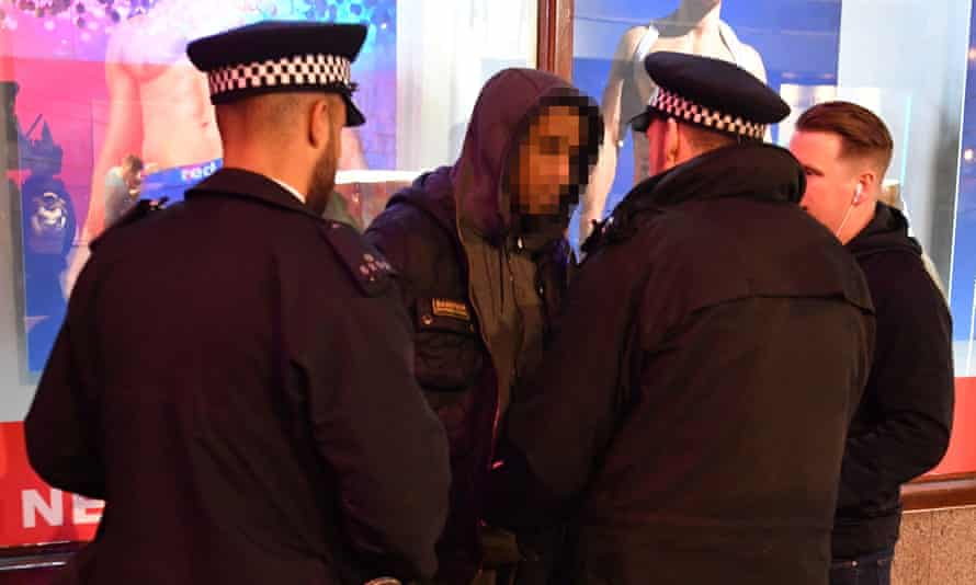 Metropolitan police officers carry out a stop and search on a man in London.