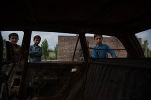 Boys peek through the windows of a burned-out car in Bacha Khan village, Khost, left devastated after a morning military raid that saw the car go up in flames