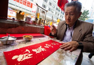 A man paints Chinese New Year 'fai chun' calligraphy couplets in gold paint as passersby crowd around him in the hope of buying one his fai chun on the last day of the Chinese Year of the Dog, in Wan Chai, Hong Kong, China