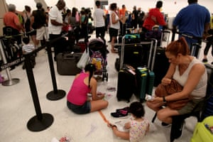 Stranded tourists and Puerto Ricans line up at the International Airport as they try to leave