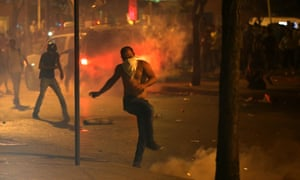 A protester kicks a tear gas canister during Sunday's clashes.