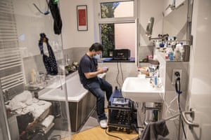 A member of the Windowflicks team sits on the edge of a bathtub in a small bathroom, while he gets the equipment ready for the movie projection