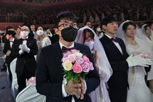 Groom in face mask holding bouquet