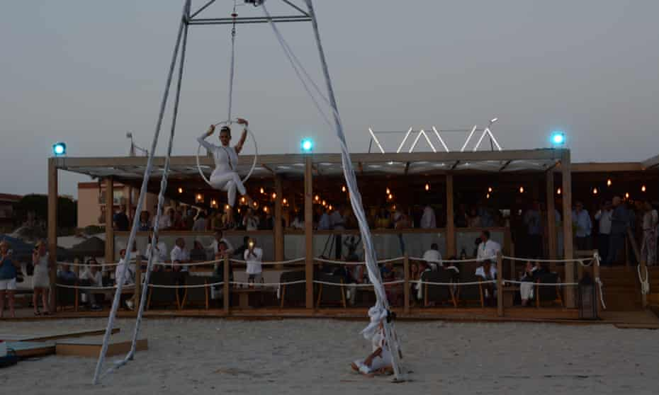 Vavá, Playa la Barrosa, Cádiz, trapeze performer on beach infront of bar at dusk