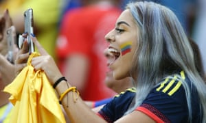 A Colombia fan takes a photograph on her mobile phone