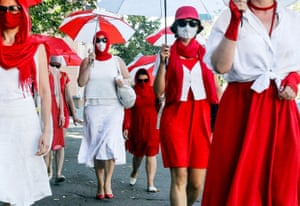 Belarusian women march down the streets holding umbrellas.