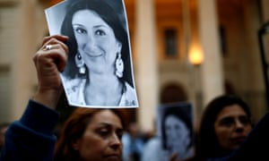 People hold up pictures of the assassinated journalist Daphne Caruana Galizia during a vigil and demonstration in Valletta, Malta