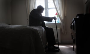 An older man silhouetted, sitting on a bed.