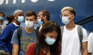 People wearing a face masks to prevent the spread of coronavirus wait to board a ferry in the port of Piraeus, near Athens.