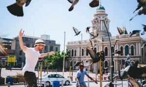 Rushay Booysen flaps at pigeons near City Hall, Port Elizabeth, South Africa