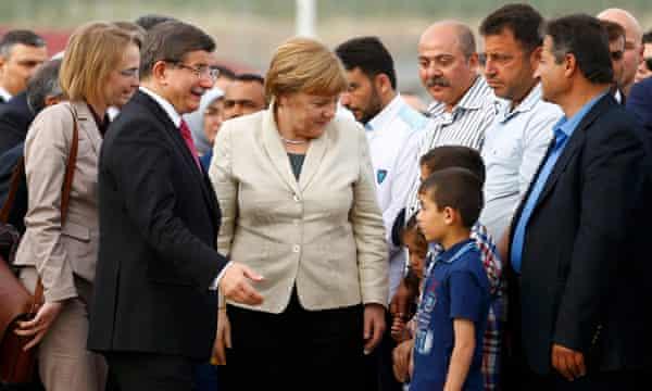 Turkish prime minister Ahmet Davutoglu and Angela Merkel speak to children in Nizip refugee camp at the weekend