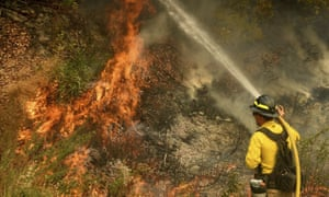A firefighter battles the El Dorado Fire, which was started by a device at a gender reveal party.