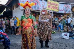 Bali, Indonesia. A police officer and a traditional dancer educate people on how to prevent the spread of Covid-19