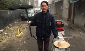 Wang Renzheng, a Chinese artist better known as Nut Brother, and the industrial vacuum cleaner he uses to suck up smog.
