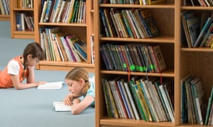 Two girls 10 12 lying on floor beside bookshelf in library reading books side viewA7MW2W Two girls 10 12 lying on floor beside bookshelf in library reading books side view