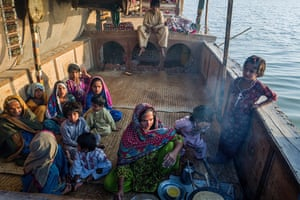 Women cautiously cook on an open fire on a boat. If the vessel were destroyed, the family would have to live on shore. A new boat costs about 1m rupees (£4,500)