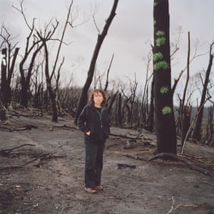 Woman stands with forest of burnt and blackened trees behind her