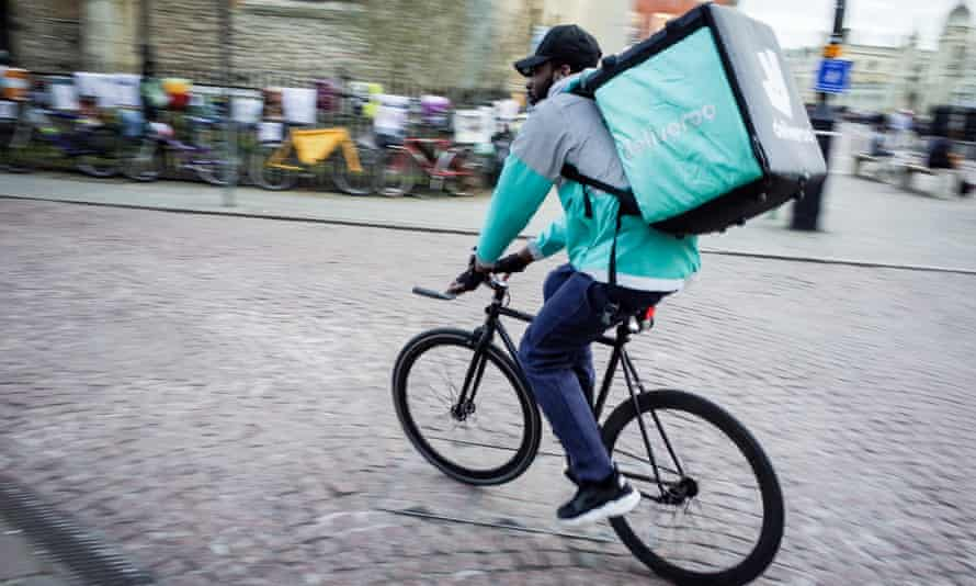 A Deliveroo food courier cycles through the streets of Cambridge.