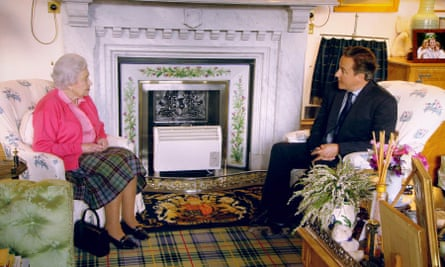 The Queen and David Cameron chat next to the thistle-tiled fireplace