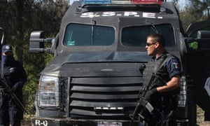 State police stand guard following a gun battle near a ranch along the Jalisco-Michoacan highway in Michoacan, a state which has also seen a mayoral candidate killed.