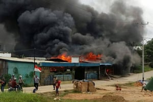 A building is set on fire by rioting demonstrators in Sorong on August 20, 2019. As Indonesian authorities were hunting for more than 250 inmates who escaped a Papua prison set ablaze during violent riots.