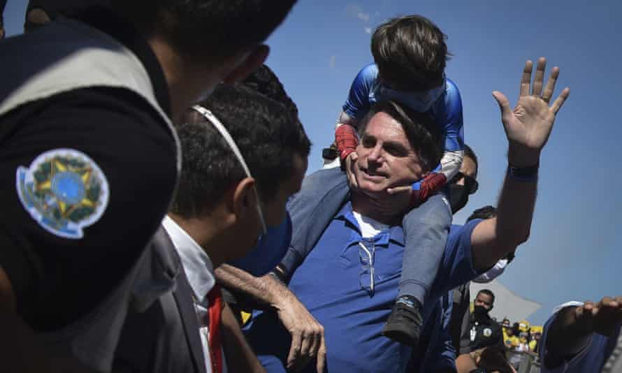 The Brazilian president, Jair Bolsonaro, carries a boy on his back as he greets supporters in Brasilia on Sunday.