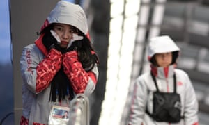 A volunteer uses handwarmers at the Winter Olympics