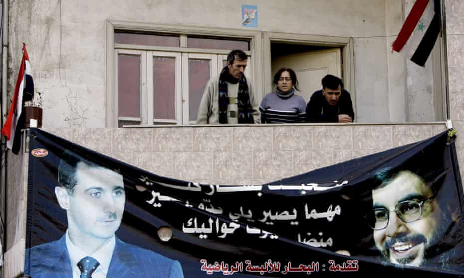 Syrians stand above a poster of President Bashar al-Assad and Lebanese Hezbollah Leader Hassan Nasrallah in an Alawite neighbourhood in the western city of Homs in 2012