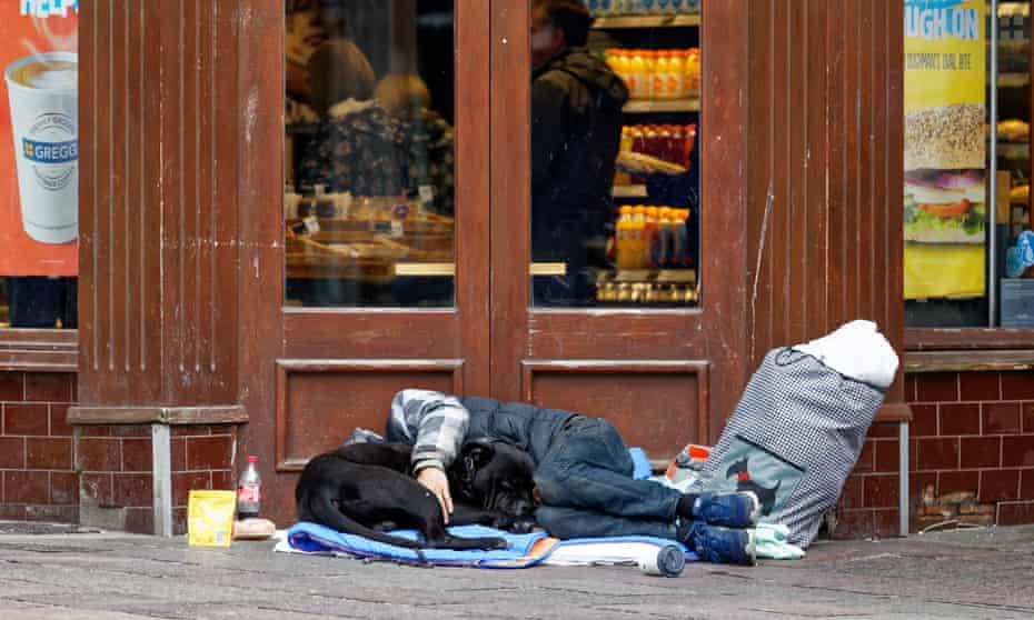 A man sleeps rough outside a bakery
