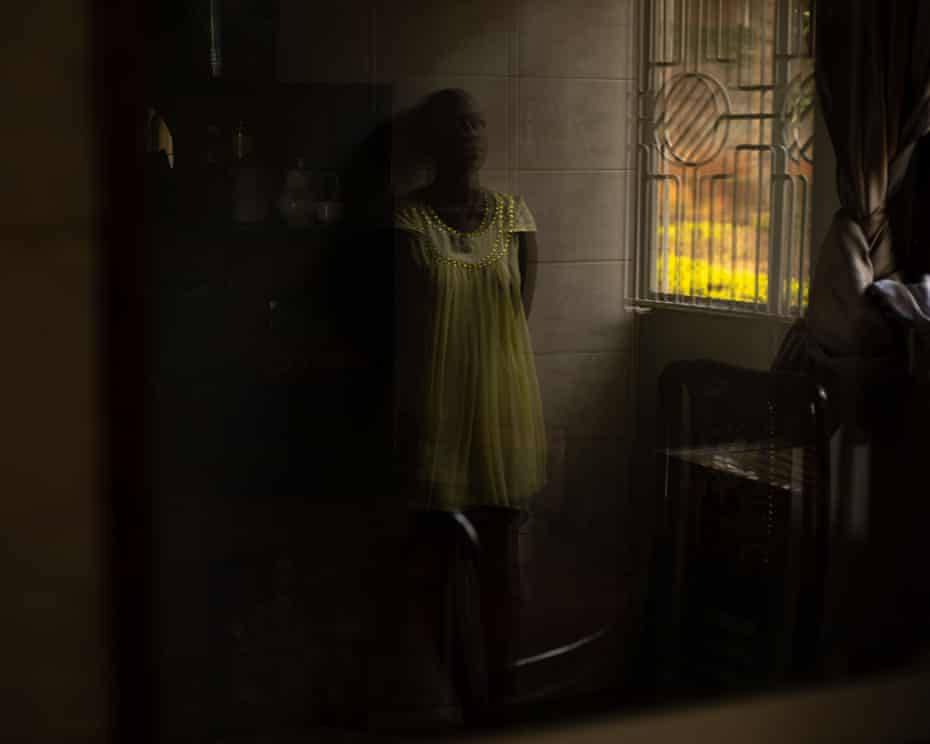 Blurry picture, standing in yellow dress by open window