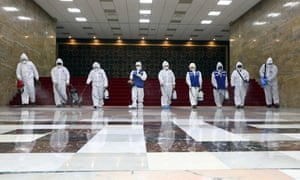 Workers from the Korea Pest Control Association spray disinfectant as part of preventive measures against the spread of the Covid-19 coronavirus, at the National Assembly in Seoul on February 25, 2020.