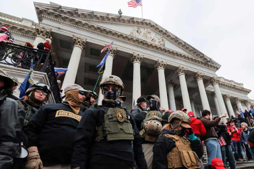 Members of the Oath Keepers militia group stand among supporters of Trump at the east front steps of the US Capitol.
