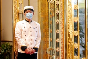 A bellboy waits to welcome guests in the lobby