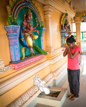 A Malaysian youth praying at a Hindu temple near her home.
