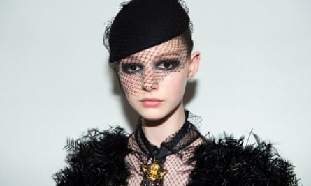 A model with smoky black eyeliner and a beret-type hat with netting over part of her face