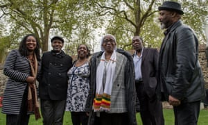 Windrush generation representatives stand outside the Houses of Parliament