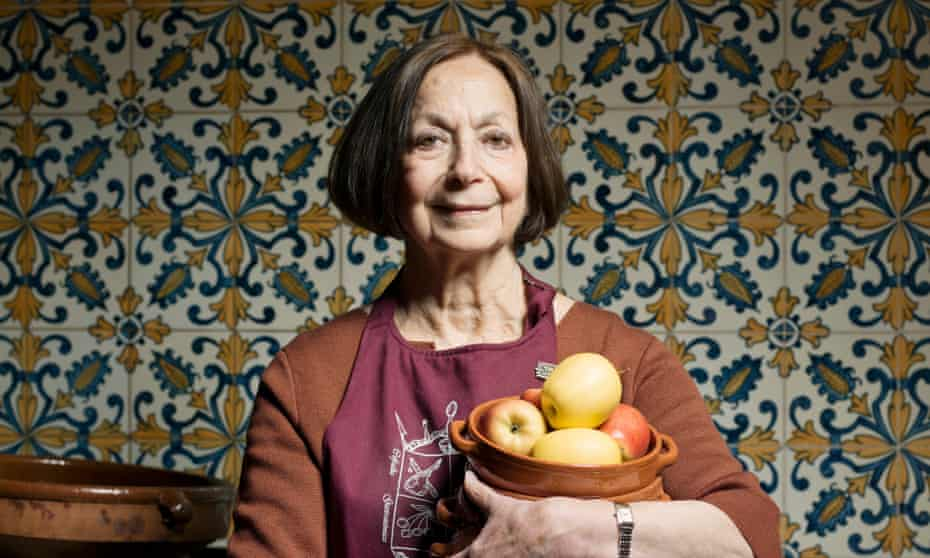 Claudia Roden at her home in an apron, a tiled kitchen wall behind, and holding a bowl of fruit