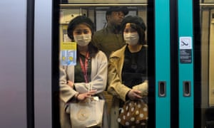 Japanese tourists wear face protection masks in the metro in Paris