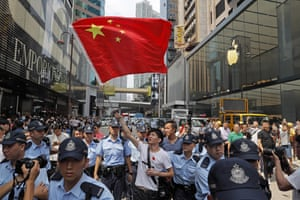 A pro-China protester is escorted out of a shopping mall by police in Hong Kong
