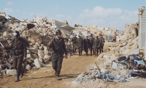 Italian firemen and rescue workers survey the ruins of Montevago, Sicily after the Belice earthquake in January 1968.