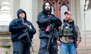 Armed protesters take part in rally on 30 April at the Michigan state capitol in Lansing, demanding the reopening of businesses shut as an anti-coronavirus measure.