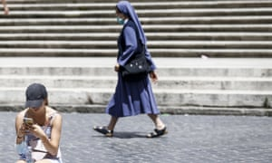 A woman checks her phone as a nun walks by, at the bottom of the Spanish Steps in Rome.