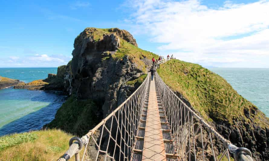 Standing on Carrick-a-Rede Rope Bridge, a famous rope bridge near Ballintoy in County Antrim, Northern Ireland, UK