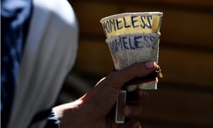 A homeless man holds a cup as he begs in Melbourne
