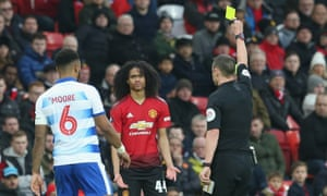 Tahith Chong of Manchester United is booked by referee Stuart Attwell.