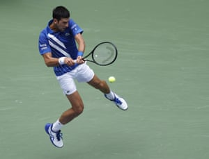 A leaping Novak Djokovic hits a return.
