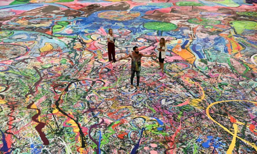 British artist Sacha Jafri (C) stands on his record-breaking painting entitled 'The Journey of Humanity' in the Emirati city of Dubai.