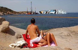 A couple sunbathe in front of the wreckage of the Costa Concordia near the harbour of Giglio Porto on 20 June 2012. Thirty-two people were killed when the cruise liner capsized after hitting rocks.